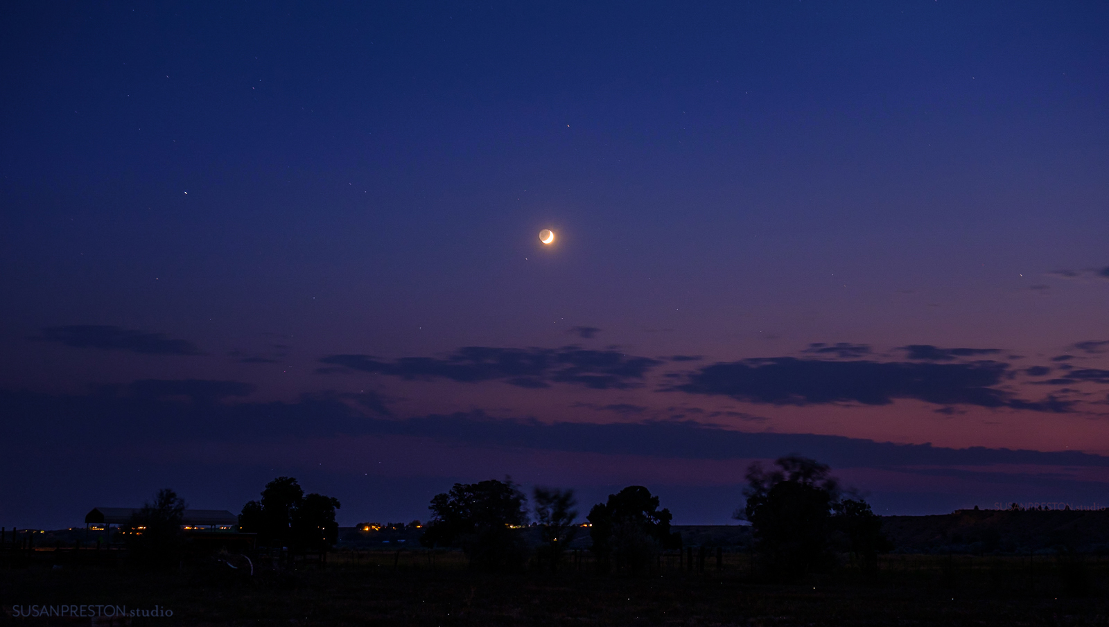 a new moon sets over Taos Valley in New Mew Mexico