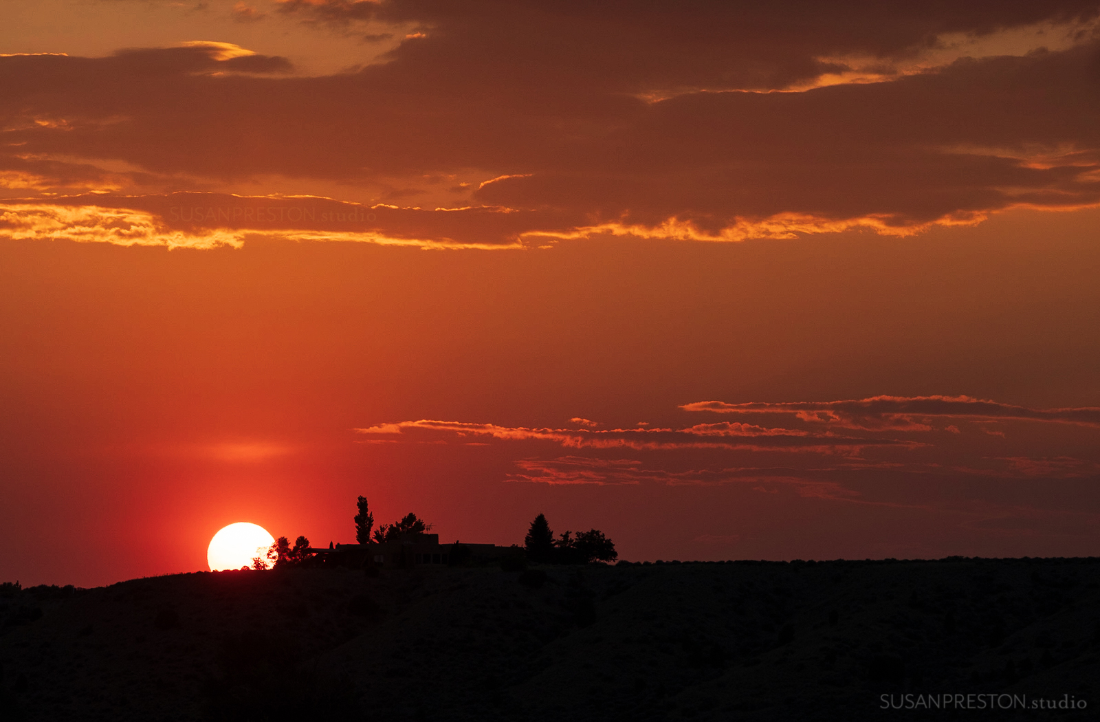 a deep red sun sets over Taos valley during a fire season in New Mexico